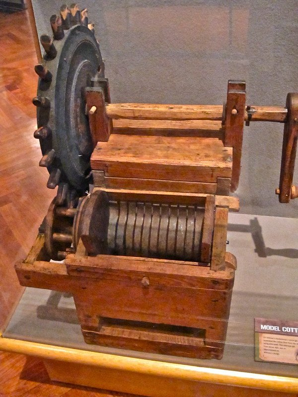 An antique cotton gin device on display in a museum.